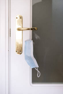 Close-up of face mask hanging on door handle - JCMF01791