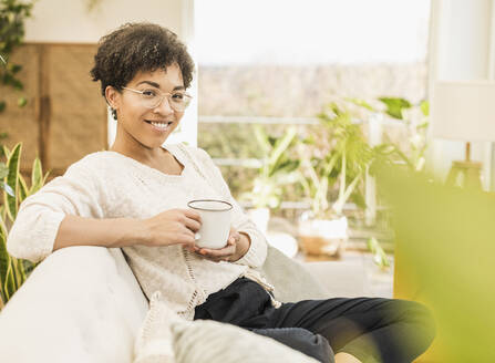 Smiling woman wearing eyeglasses drinking coffee while sitting at home - UUF22606