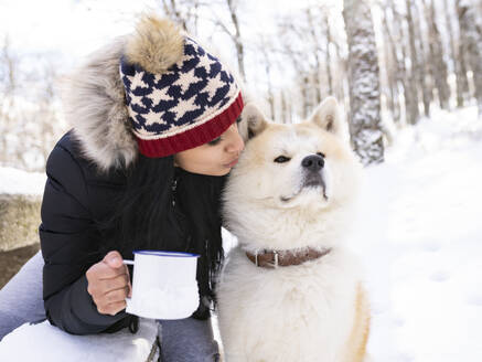 Mid adult woman with coffee cup kissing dog while sitting on bench in snow - JCCMF00844