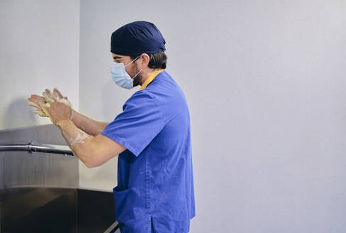 Male doctor wearing face mask washing hands while standing at hospital - SASF00136