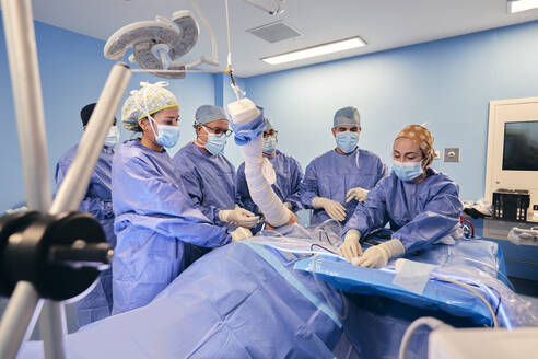 Doctors wearing face mask doing arthroscopic surgery of patient while standing by table at operating room during COVID-19 - SASF00142