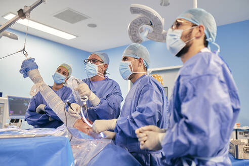 Surgeon with endoscope equipment operating shoulder arthroscopy while standing with colleague in operating room during COVID-19 - SASF00151