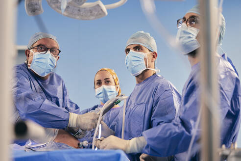 Professionals with endoscope surgical equipment operating surgery while standing in operating room during COVID-19 - SASF00157