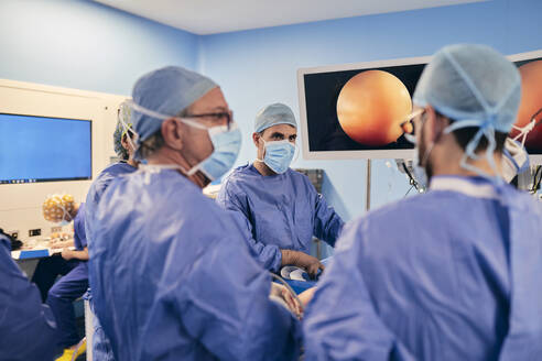Surgeons wearing face mask having discussion while operating surgery in operation room - SASF00166