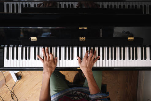 Young male musician playing piano at home - JCMF01813