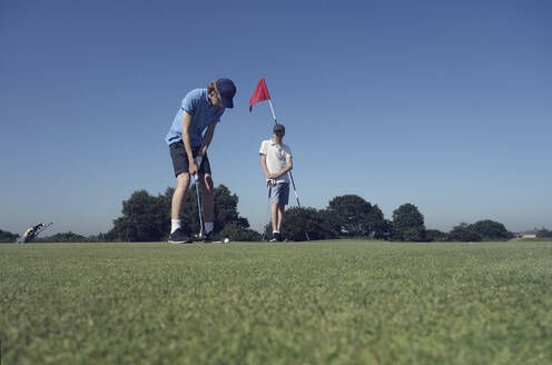 Friends playing golf against clear blue sky on course - AJOF00982