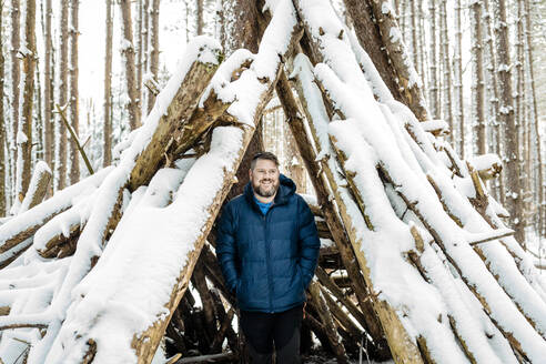 Smiling man standing with hands in pockets in teepee covered with snow at forest - AWAF00031