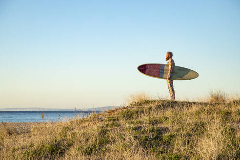 Man looking at sea view while standing with surfboard on beach - KBF00671