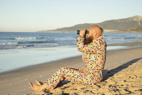 Man wearing colorful suit using binocular while sitting on beach - KBF00683