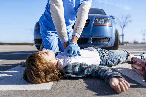 Rescue worker using giving CPR to victim lying on road after car accident - GGGF00859