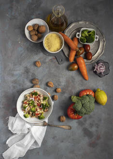 Top view of bowl with healthy homemade bulgur couscous salad with various vegetables and walnuts served on table with ingredients - ADSF20001