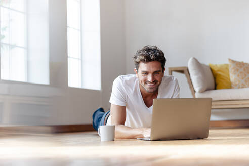 Man smiling while working on laptop at home - SBOF02370
