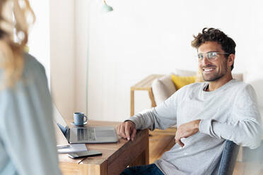 Smiling man wearing eyeglasses looking at his girlfriend while sitting at home office - SBOF02412