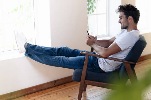 Man using mobile phone phone while sitting with legs crossed at ankle on window at home - SBOF02448