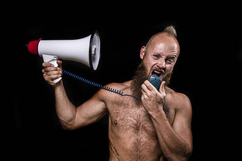 Frustrated male shirtless viking screaming on himself through megaphone against black background - KBF00692