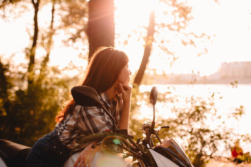 Young woman looking at view sitting on motorcycle relaxing by river - CAVF91692