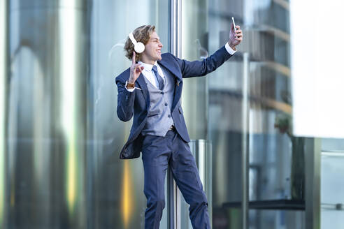 Happy male professional gesturing while taking selfie through smart phone against office building - GGGF00890