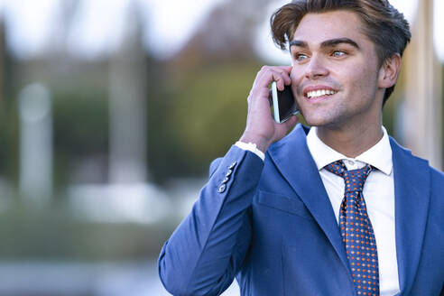Smiling young businessman communicating on mobile phone - GGGF00896