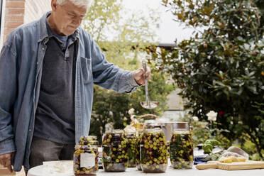 Senior man preparing olives in jars on table at back yard - AFVF08055