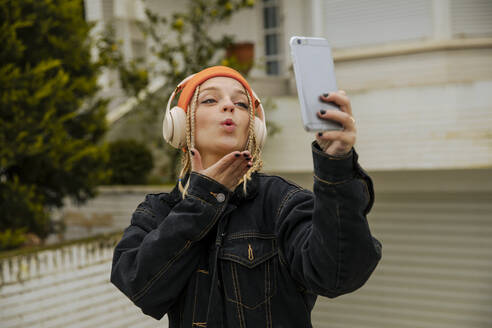 Fashionable woman blowing kiss while taking selfie through mobile phone - ACPF01041