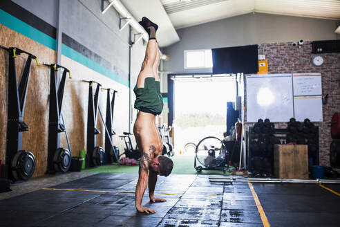 man doing Free handstand hold in a crossfit gym - spain, andalusia, almeria - MIMFF00420