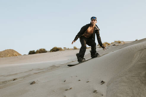 young man snowboarding on sand dunes - spain, andalusia, almeria - MIMFF00438