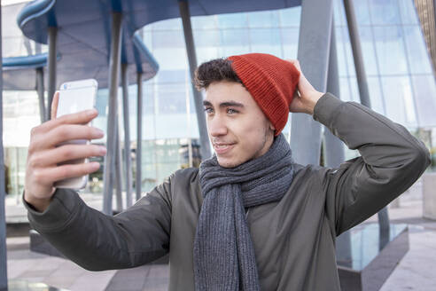 Young man wearing knit hat taking selfie through mobile phone in city - IFRF00312