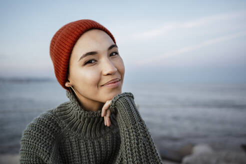 Smiling woman sitting with hand on chin against sky - RCPF00616