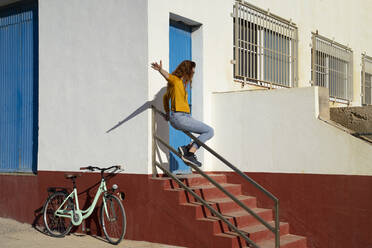 Young woman sliding on railing by white built structure during sunny day - AFVF08059