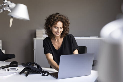 Smiling businesswoman working on laptop while sitting at desk in office - PESF02502