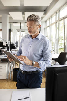 Businessman using digital tablet while standing at open plan office - PESF02532