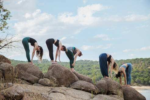 Young women with instructor practicing Uttanasana yoga on rock - MRRF00795