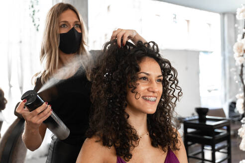 Hairstylist in protective mask fixing hairdo of happy curly haired female client with hair spray in modern hairdressing studio - ADSF20112