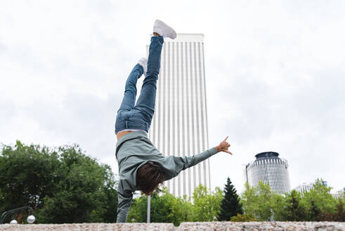 Young man gesturing shaka sign while doing handstand in city - JMPF00790