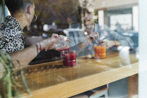 Friends pouring drink in glass while sitting at restaurant - JRVF00124