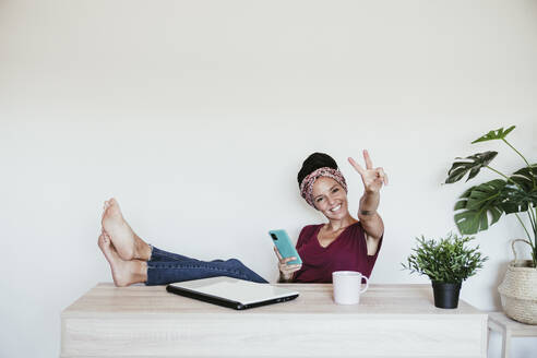 Cheerful female entrepreneur making peace sign while relaxing with feet up at home office - EBBF02217