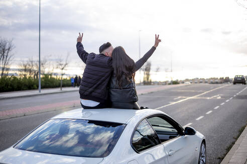 Carefree couple gesturing peace sign while sitting n car rooftop - OCMF01999