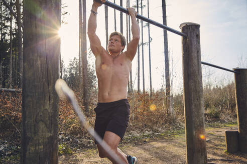 Shirtless male athlete hanging on horizontal bar on fitness trail in forest - KDF00739