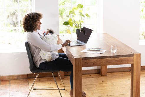 Mid adult woman holding baby while working on laptop at home - SBOF02469