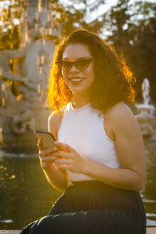 Smiling woman wearing sunglasses using smart phone while sitting against fountain during sunset - JMPF00819
