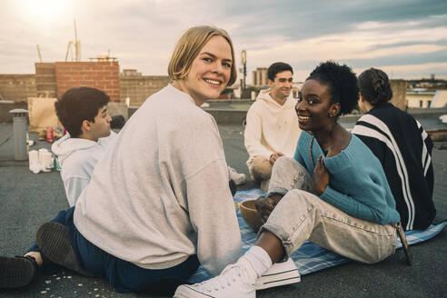 Portrait of female friends enjoying on building terrace during sunset - MASF21334