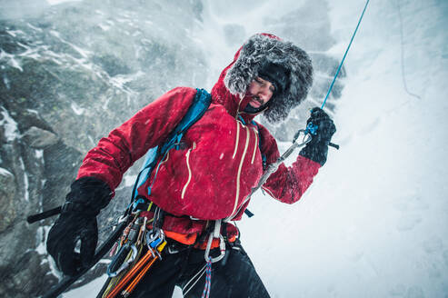 A male ice climber pulls a rope after climbing and rappelling a route - CAVF92075