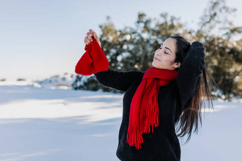 Woman with long hair holding knit hat while standing on snowy land at countryside - MRRF00820