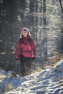 Woman walking in forest in Winter - MRF02452