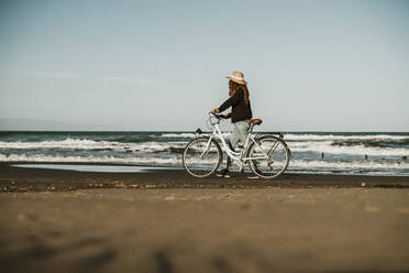 Young woman walking with bicycle by water waves at Fangar Beach, Ebro delta, Spain - AFVF08075