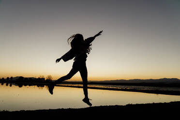 Carefree young woman with arms raised dancing during dusk at Ebro Delta, Spain - AFVF08078