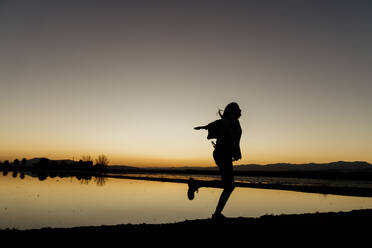 Young woman twirling on one leg during sunset at Ebro Delta, Spain - AFVF08081