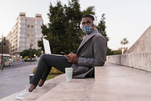 Young man wearing face mask and headphone using mobile phone while sitting with laptop on steps - EGAF01522