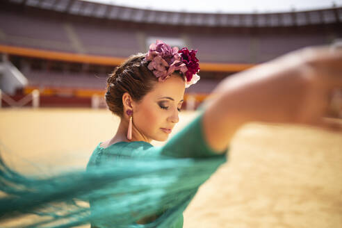 photo of a woman dressed in flamenco and with flowers on her head. she is moving the fringes of her dress with the wind - spain, andalucia, almeria - MIMFF00494