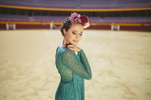 young woman dressed in a flamenco dress and flowers on her head in a bullring - spain, andalucia, almeria - MIMFF00497